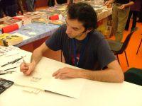 Gipi a Lucca mentre disegna una dedica